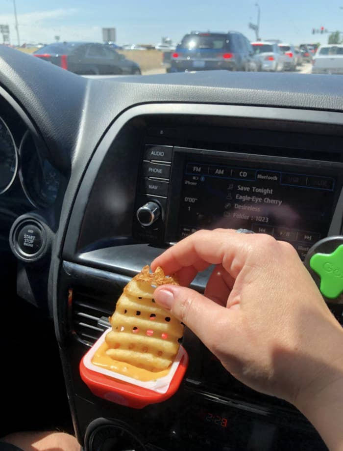 reviewer dipping fry into sauce that's placed in the dip clip and attached to car vent