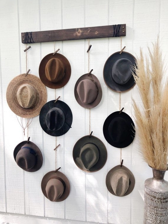 Hanging hat organizer with colorful fedoras clipped to pins on dangling ropes