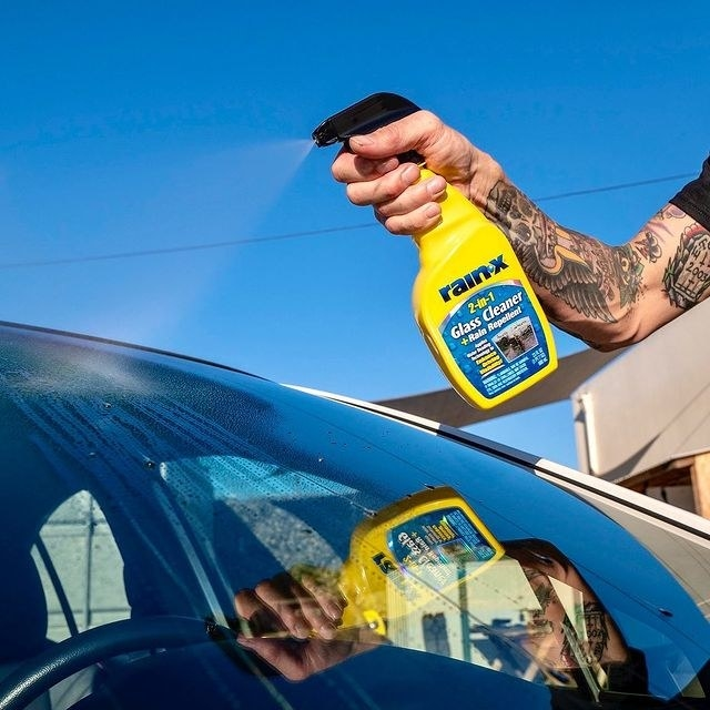 The cleaner being sprayed on to a windshield