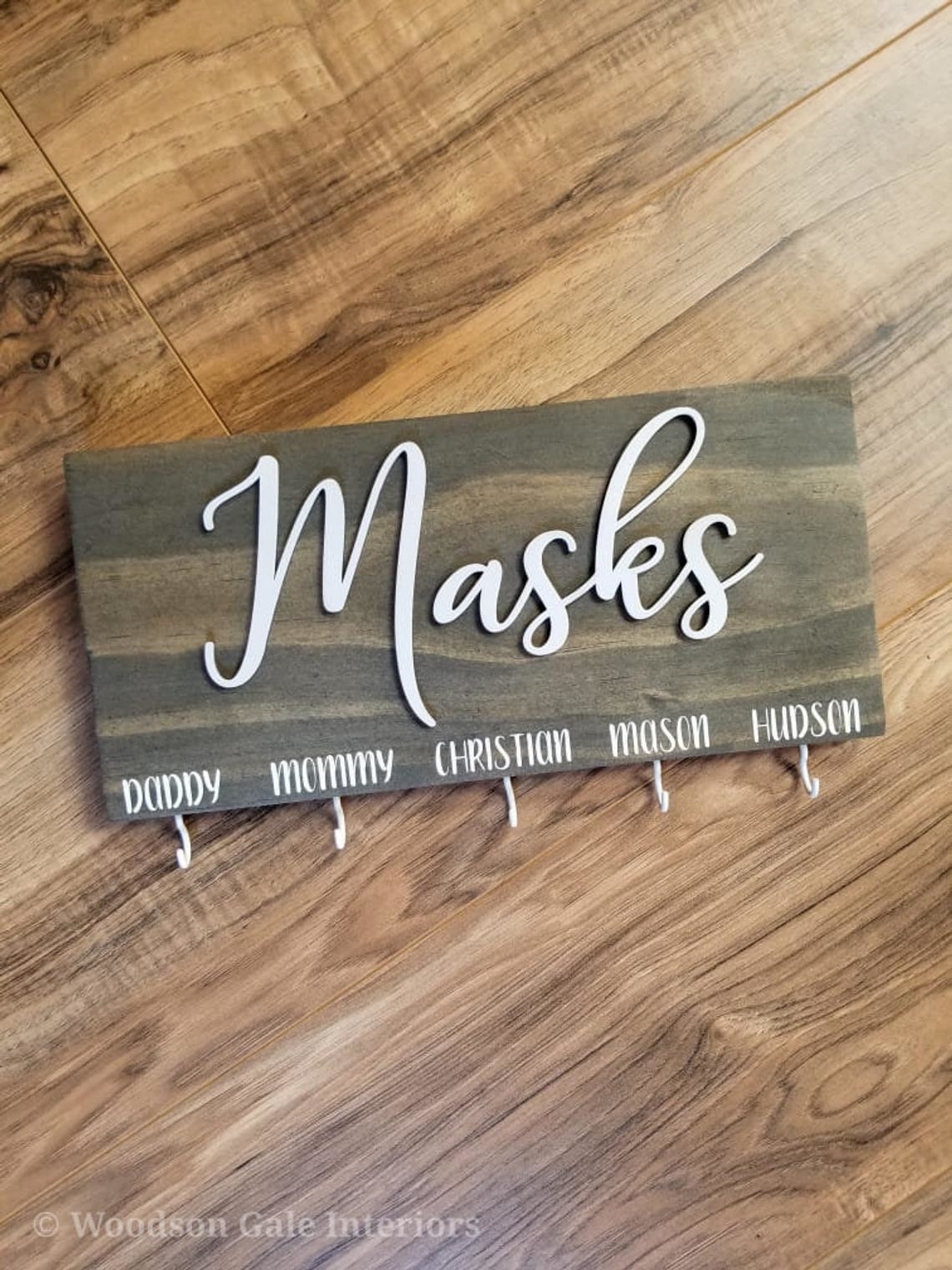 """wood sign that says """"masks"""" in white script, with five hooks along bottom, each labeled with a household member's name"""