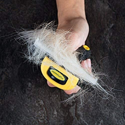 A person holding up the deshedding tool with loose fur on it