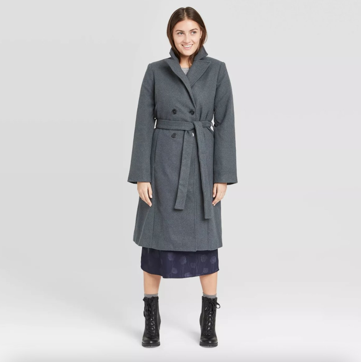 The coat on a model wearing a dark blue dress and lace-up black booties