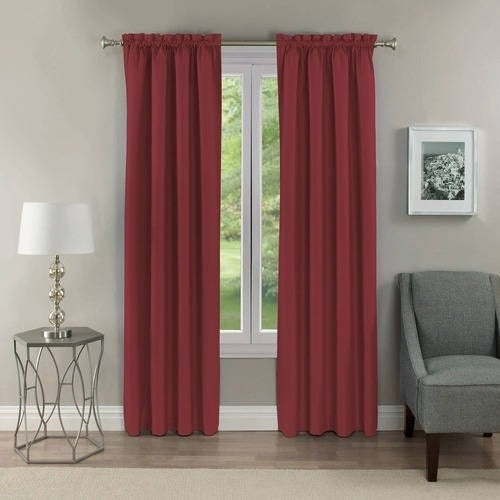 The curtains in burgundy, hung over white windows