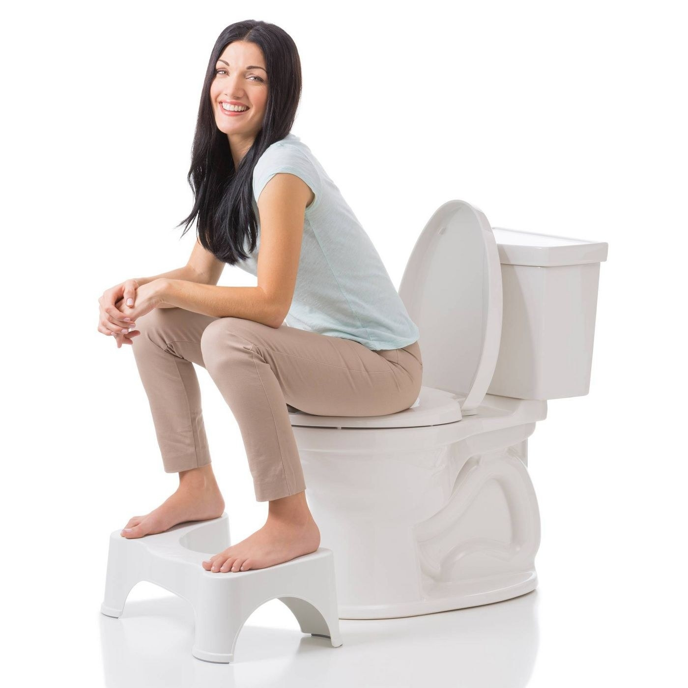 A person sitting on a toilet with a squatty potty