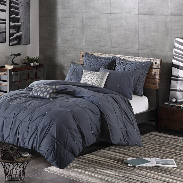 The comforter set in navy, with tufting on the comforter and also on the pillow shams