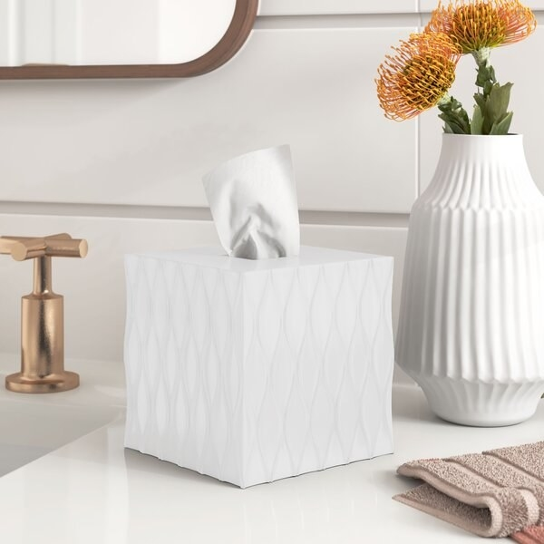 The tissue box cover, which is white, square, and has a geometric design carved into it