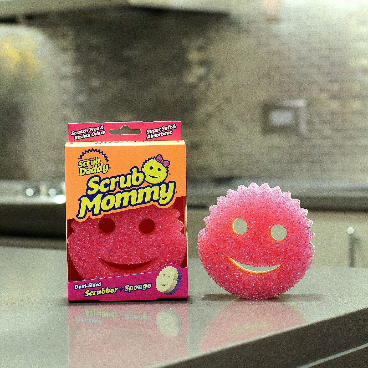 The Scrub Mommy in its package, and another one out of the package, on a kitchen island countertop