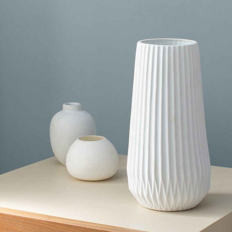 The vase, which is white, and has an accordion-folded-style texture