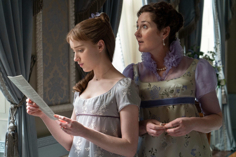 Daphne Bridgerton reads the latest letter written by Lady Whistledown as Viscountess Bridgerton looks on