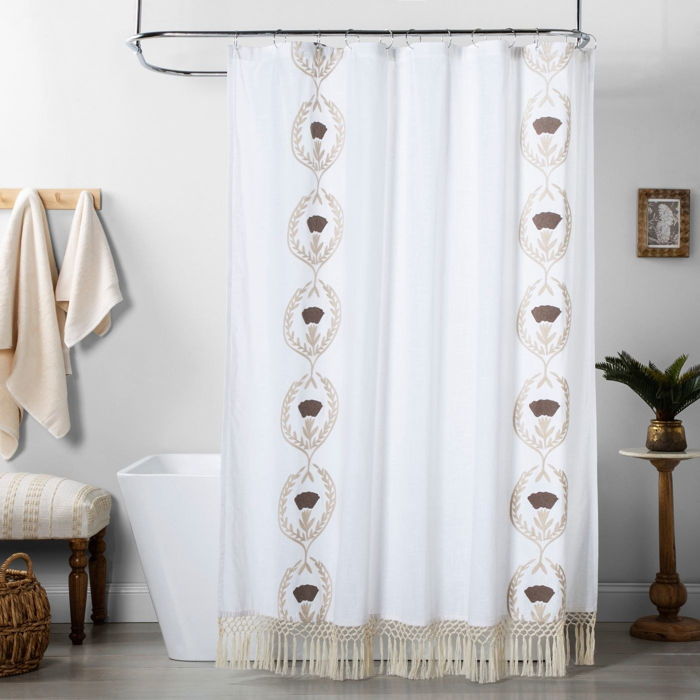 a white shower curtain with tan fringe on the bottom and a wheat-like vertical design