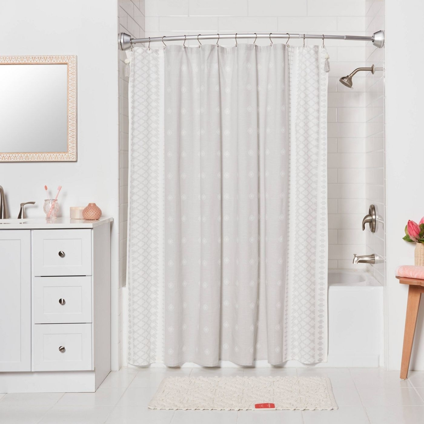 The rod installed in a bathroom with a white shower curtain on it