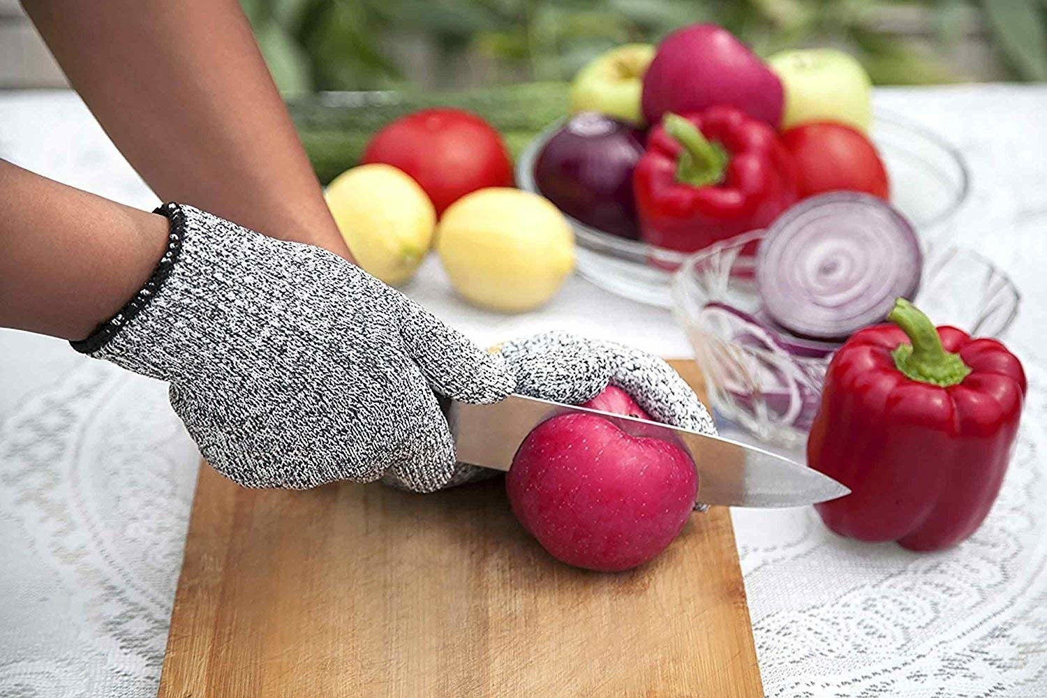 A hand with anti-cut gloves cutting a fruit