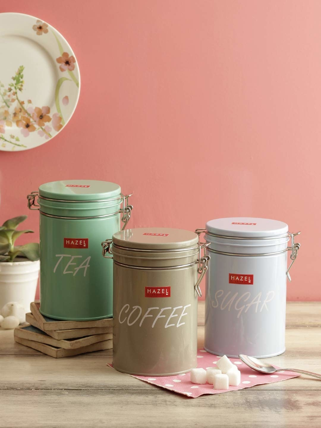 Tea, coffee and sugar canister next to a pink background