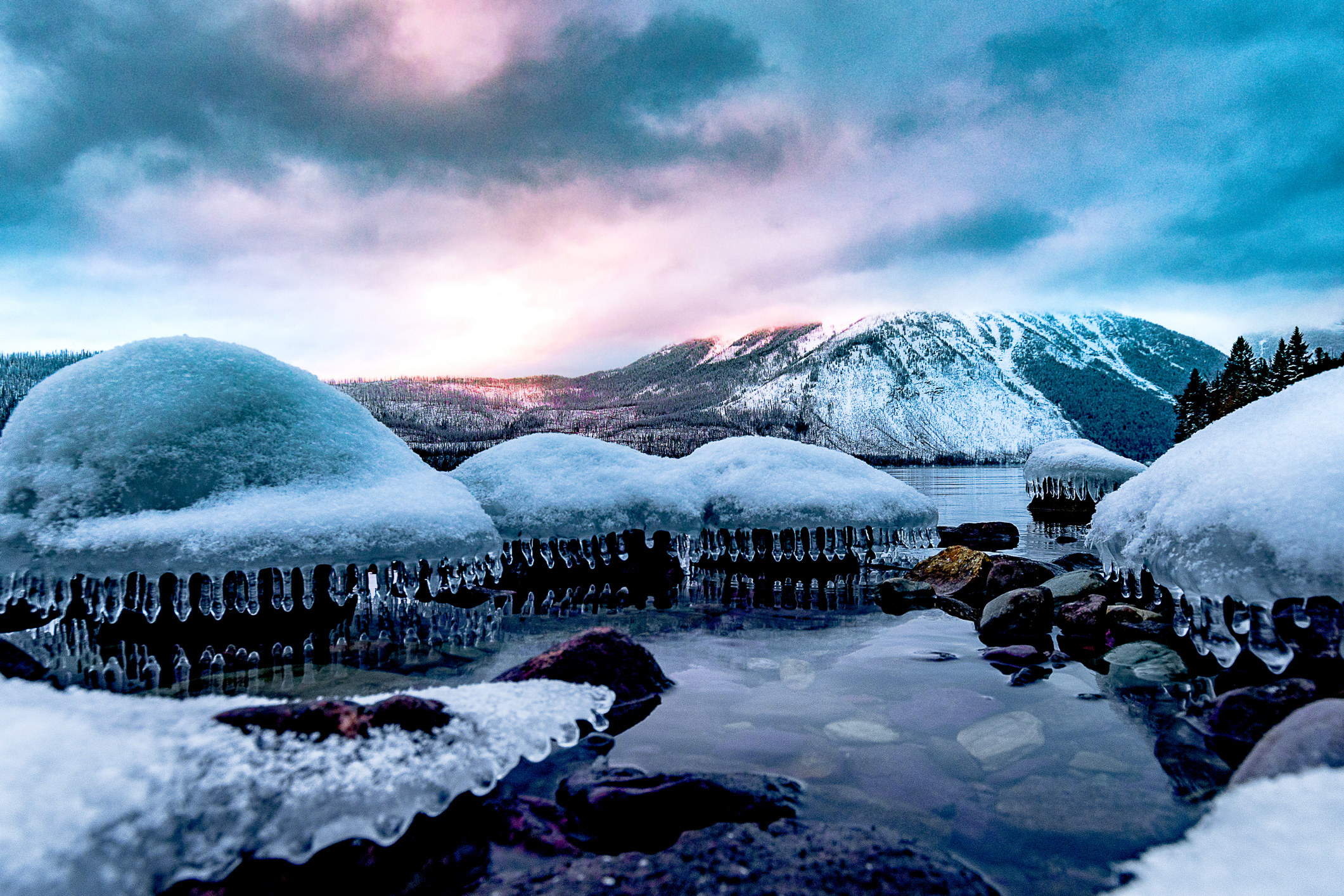 snow covered rocks on an icy lake
