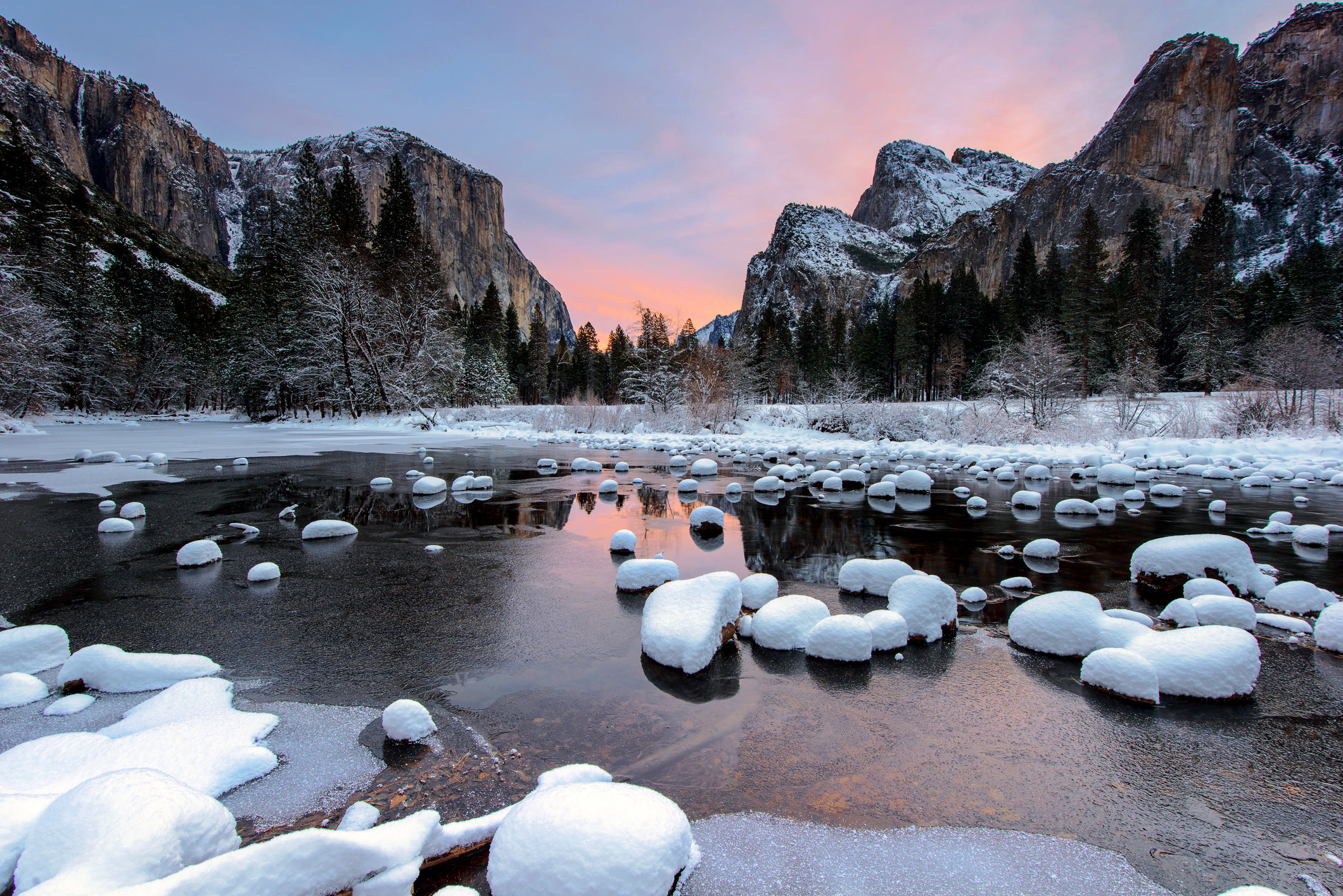 Snow covered rocks in a river with mountains in the background