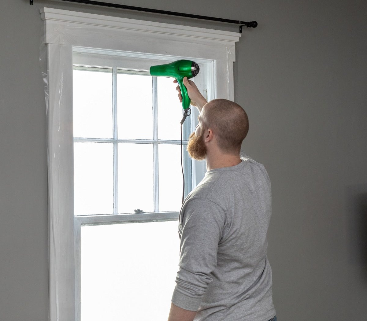 A man installing the window insulation