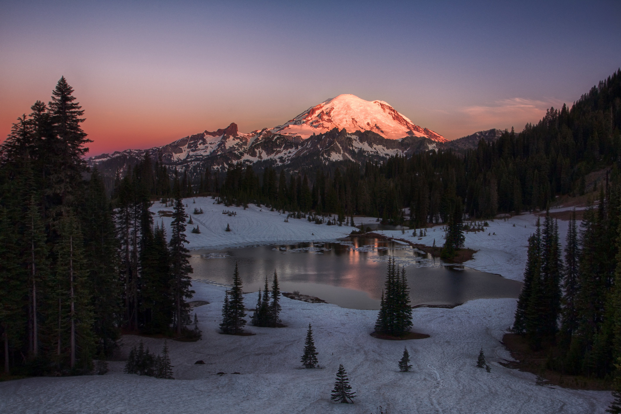 Snow covered mountain towers above a lake