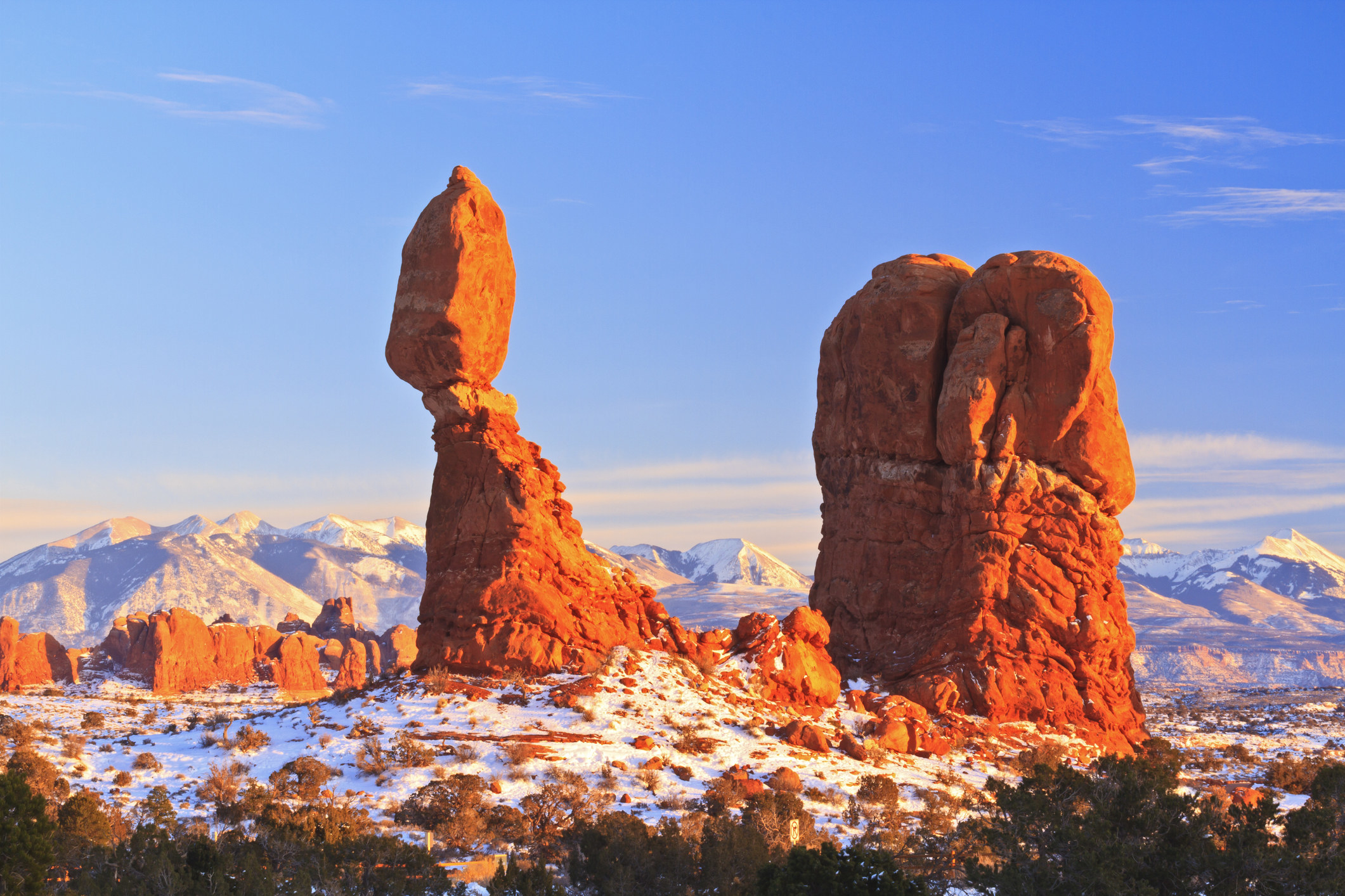 Light hits red rock spires in a snowy open space