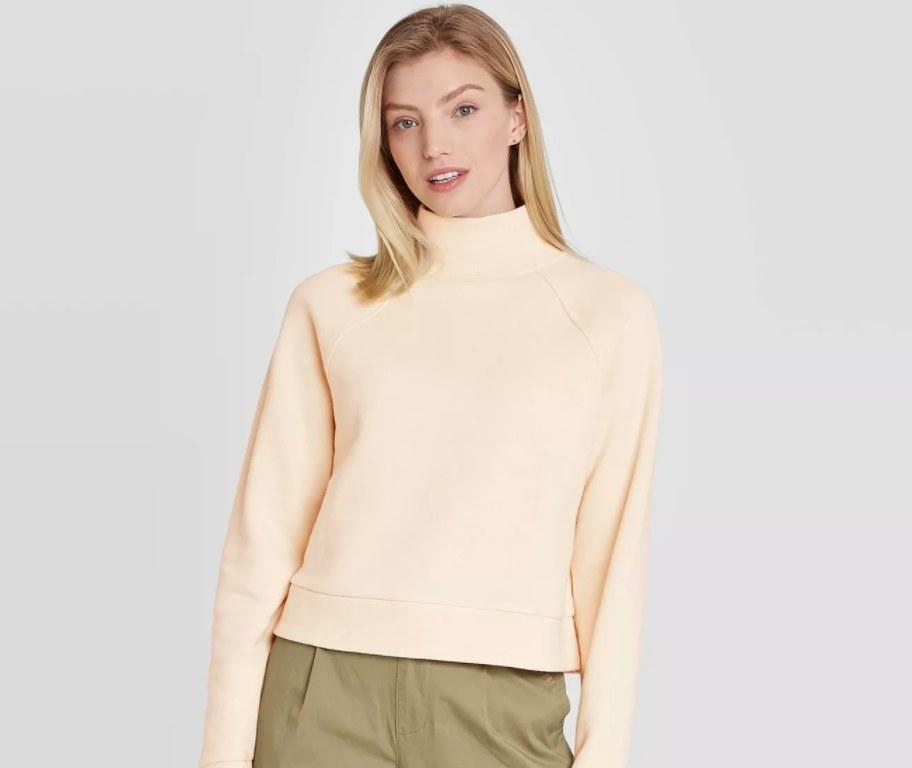 The pullover in the color cream