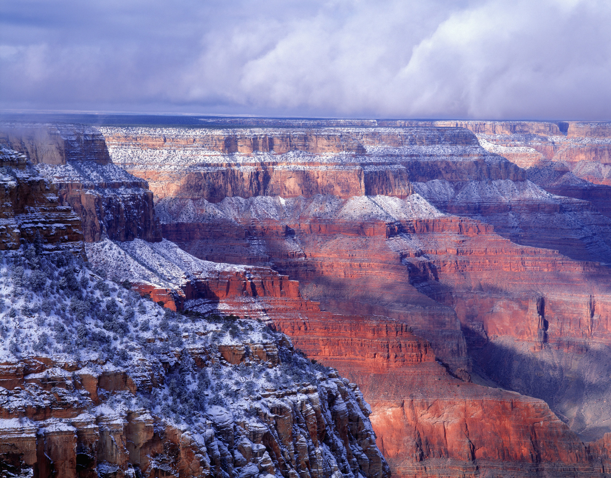 red rocky cliffs of the grand canyon dusted with snow