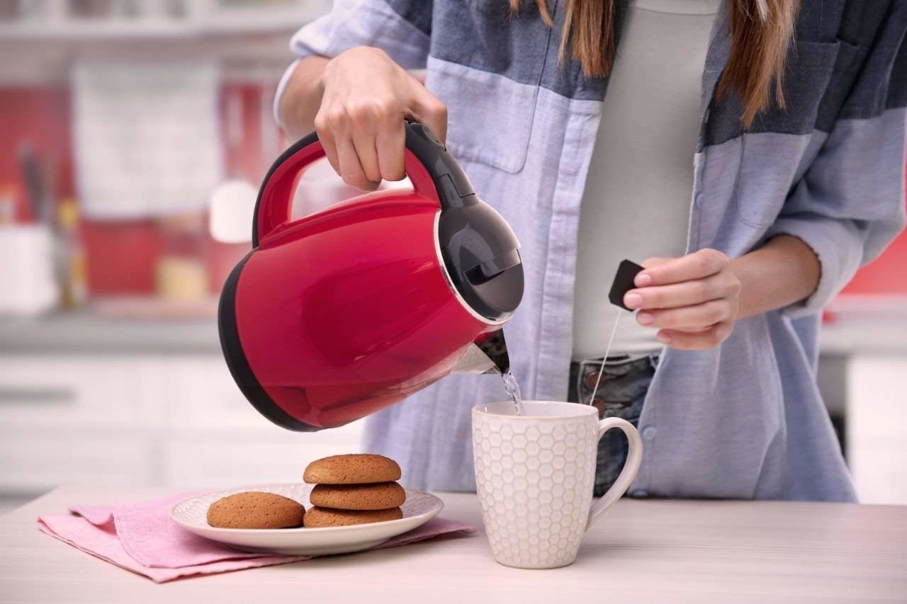 A kettle pouring water in a tea mug