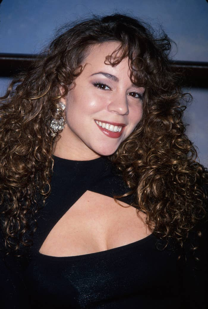 Mariah Carey smiling with her hair curly and in a cut-out black dress