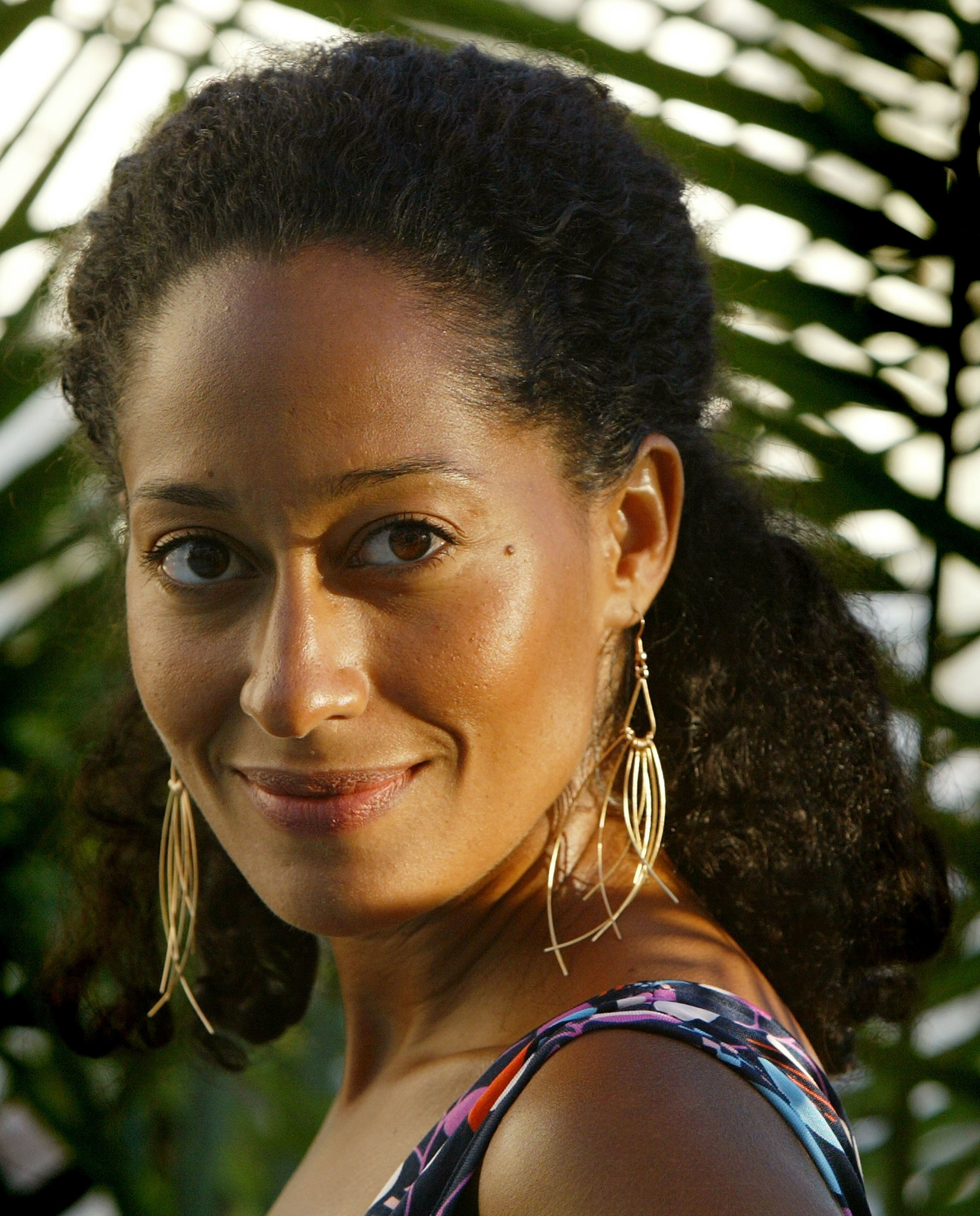 Tracee Ellis Ross with her natural hair half-up, half-down, smiling