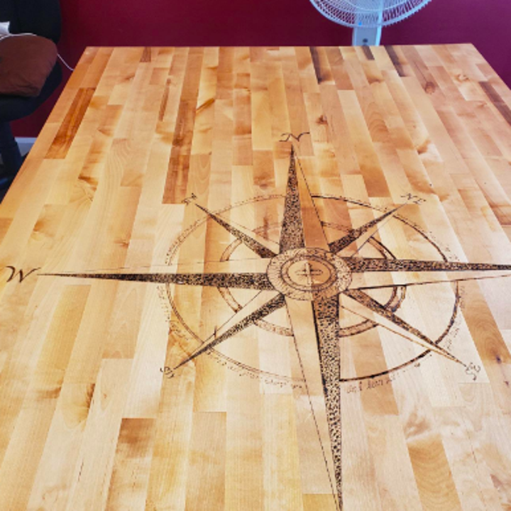 Reviewer's rose compass burned into tabletop