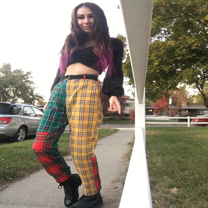 reviewer wearing the pants with yellow plaid left leg and red and green plaid on the right leg