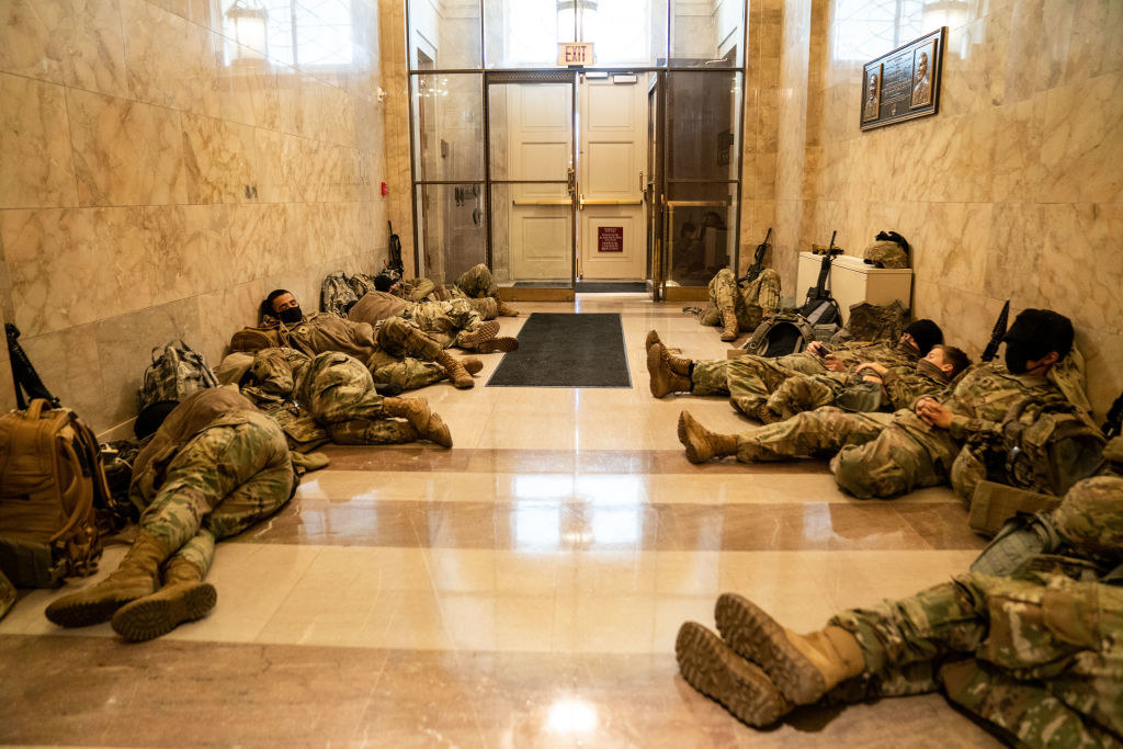 National Guard members rest on the floor with their weapons next to them in the Capitol