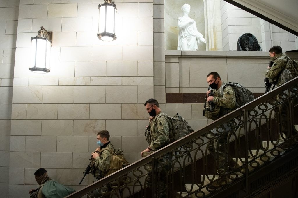Armed National Guard members walk down a stairwell