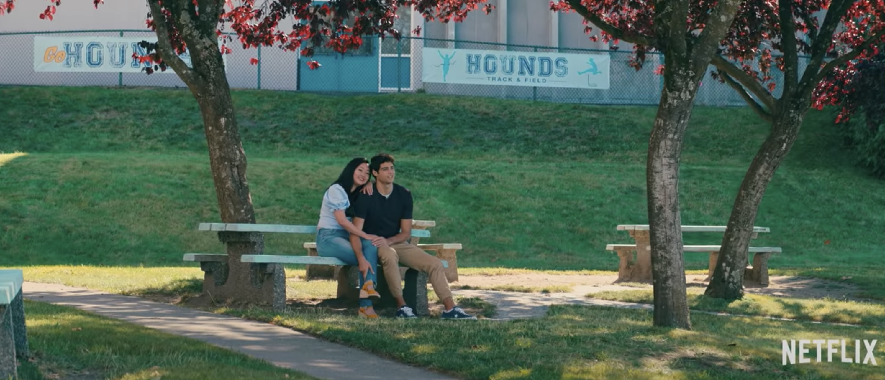 Lara Jean and Peter sitting at a table outside at their high school
