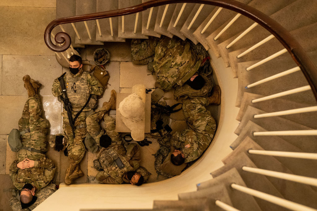 An overhead shot of National Guard members sleeping in the nook of a stairwell inside the Capitol