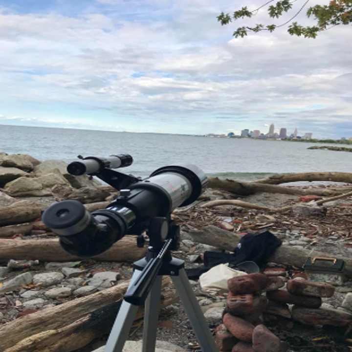 Reviewer image of telescope on beach pointing toward small city skyline in distance