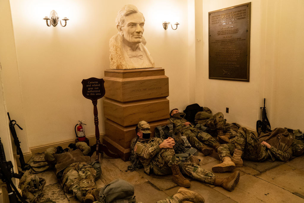 Armed National Guard members lie on the floor and against a bust of President Abraham Lincoln inside the Capitol
