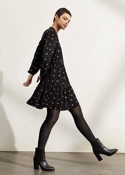 Model in black star print dress