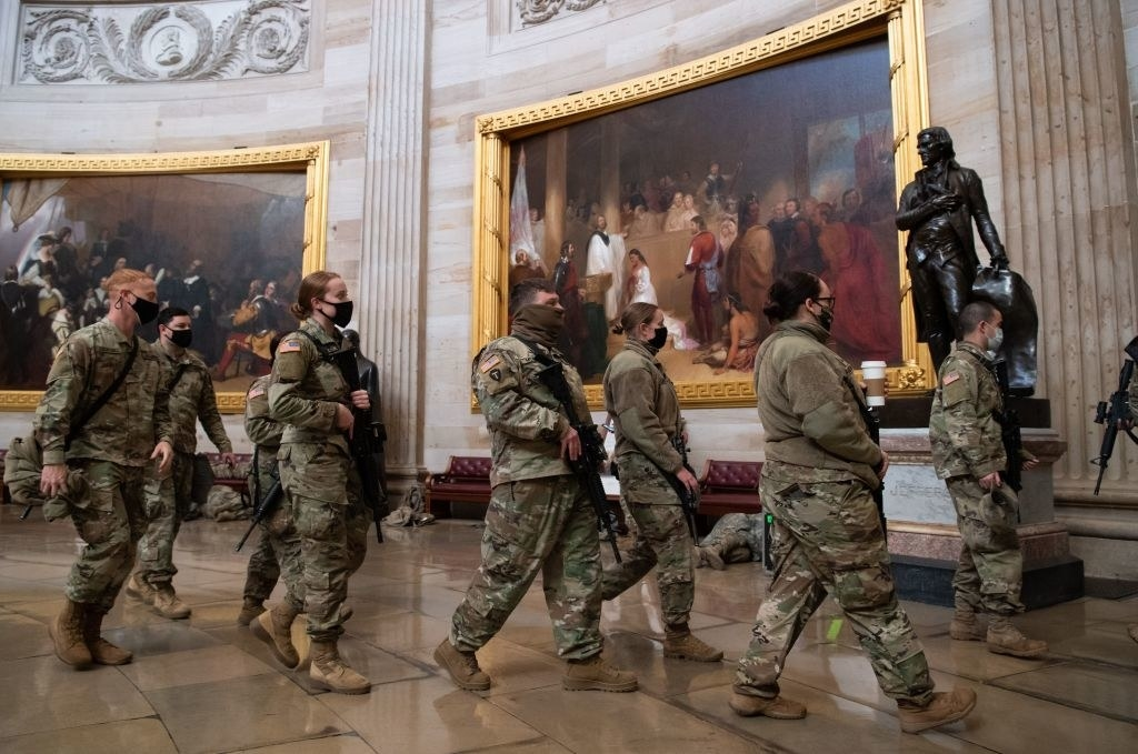 Armed National Guard members walk out of a room in the Capitol