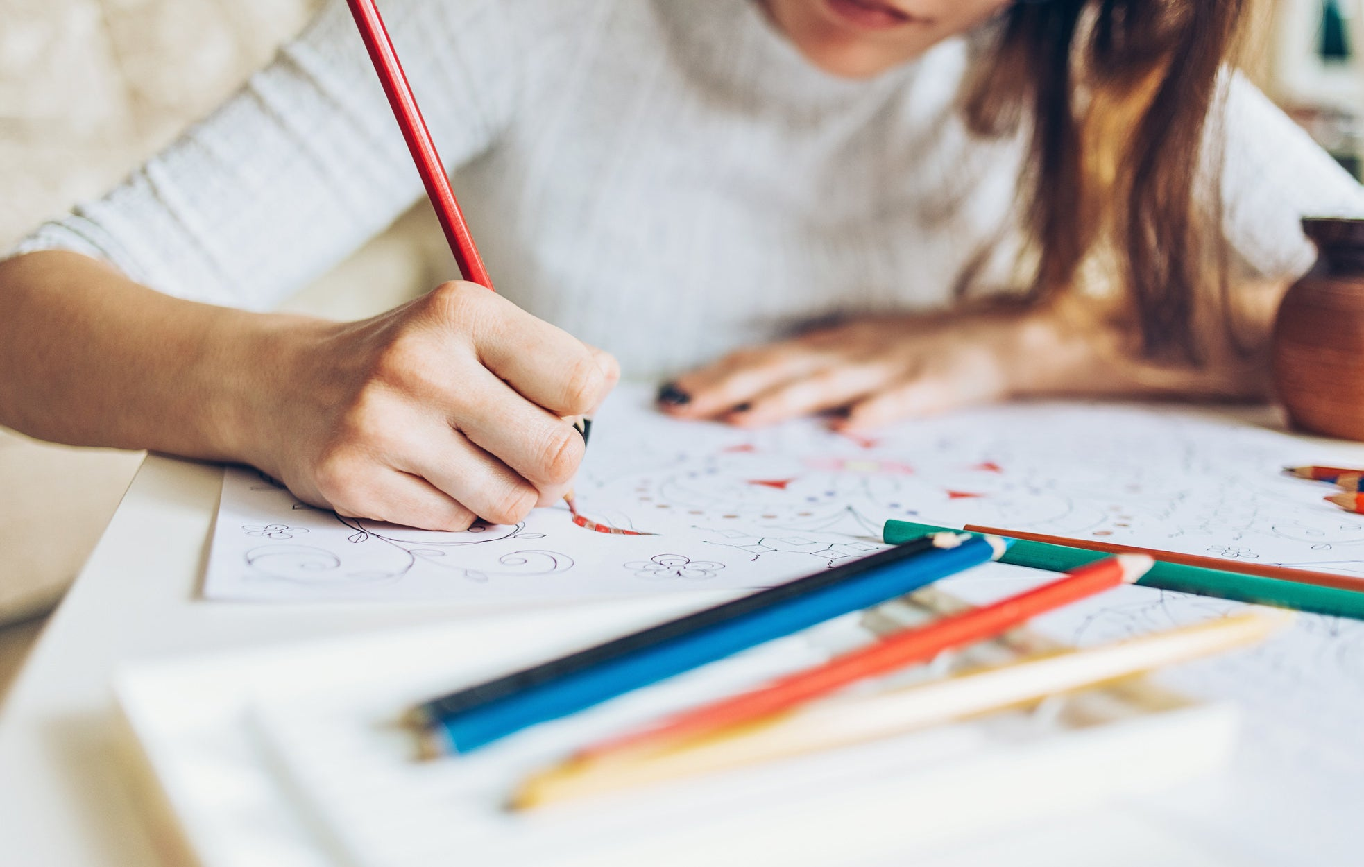 A woman coloring with colored pencils.