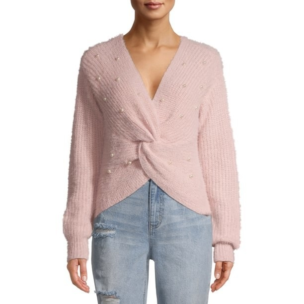 a model in a pink sweater with a twisted design in the front and pearl accents