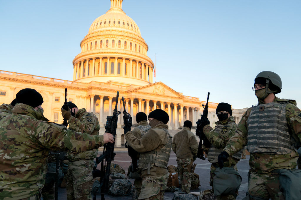 Several National Guard members holding their weapons as they stand outside of the Capitol