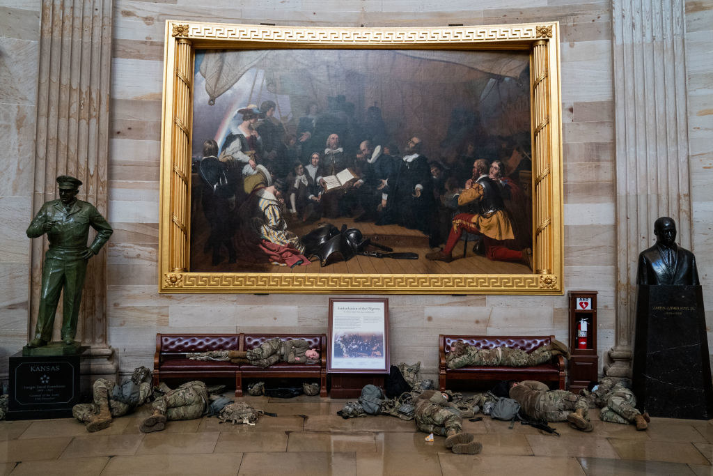 Two National Guard members lie on benches in front of a massive painting flanked by a bust and a statue inside the Capitol