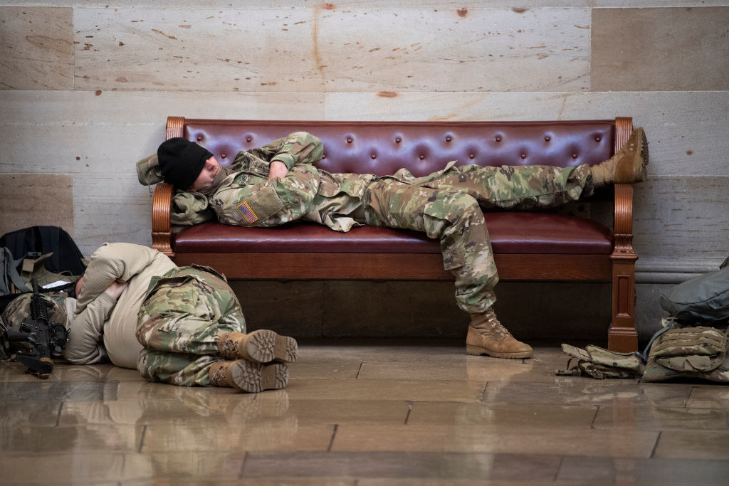 A National Guardsman lies on a bench with their hat over their eyes