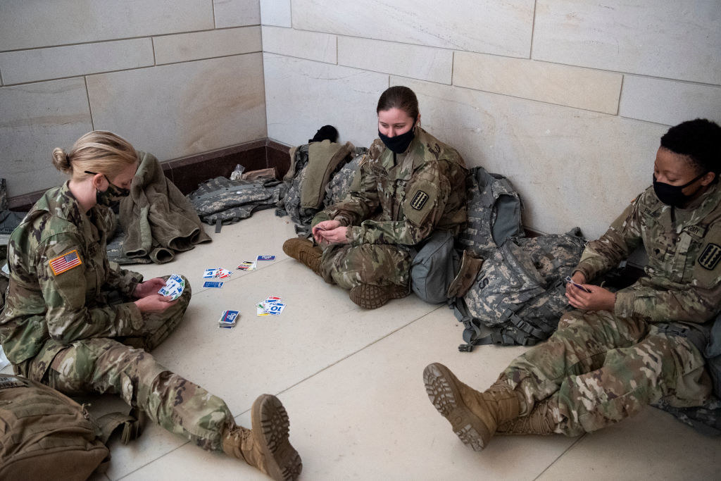 National Guard members play cards as they sit on the floor of the Capitol