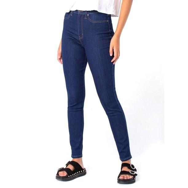 Model in ultra high rise skinny jeans with a faux pocket