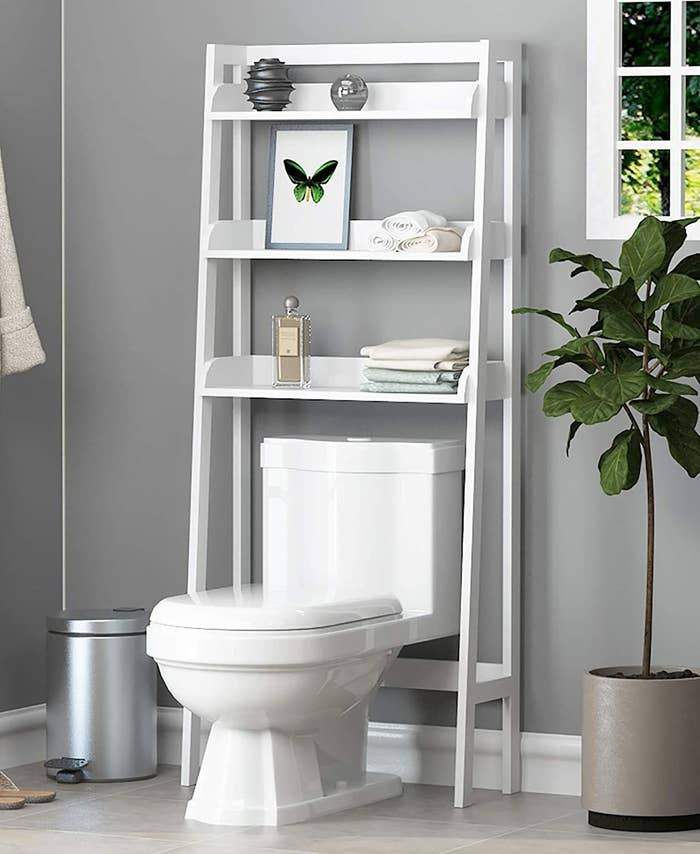 Over-the-toilet bathroom shelving unit with various items placed on shelves
