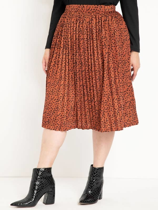 Model in orange pleated midi skirt