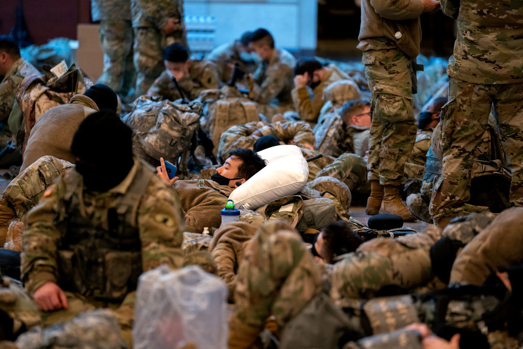 A National Guard member lies on a pillow as he looks through his phone in the Capitol