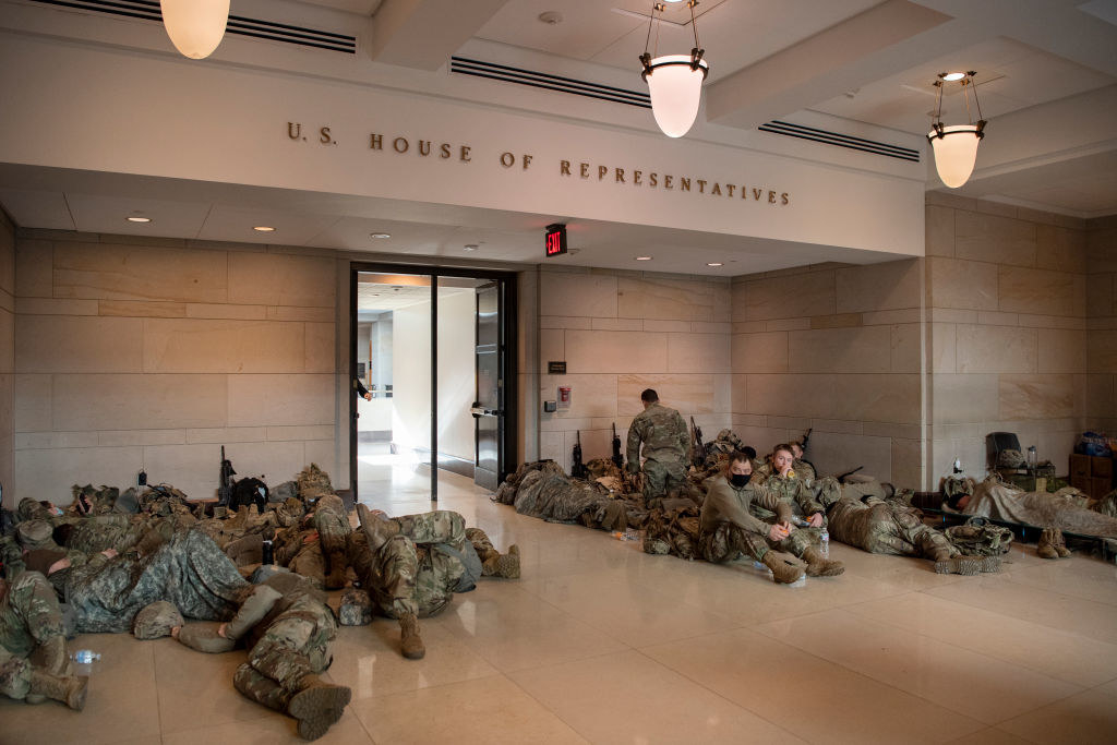National Guards members lie and sit in front of an open door with the words US House of Representatives above it