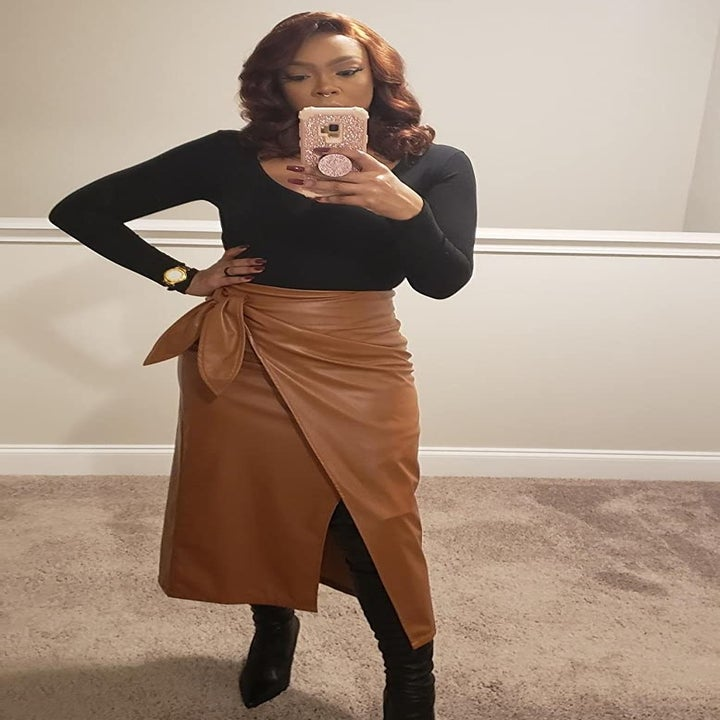 A reviewer wearing the skirt with a slit and a tie waist in brown