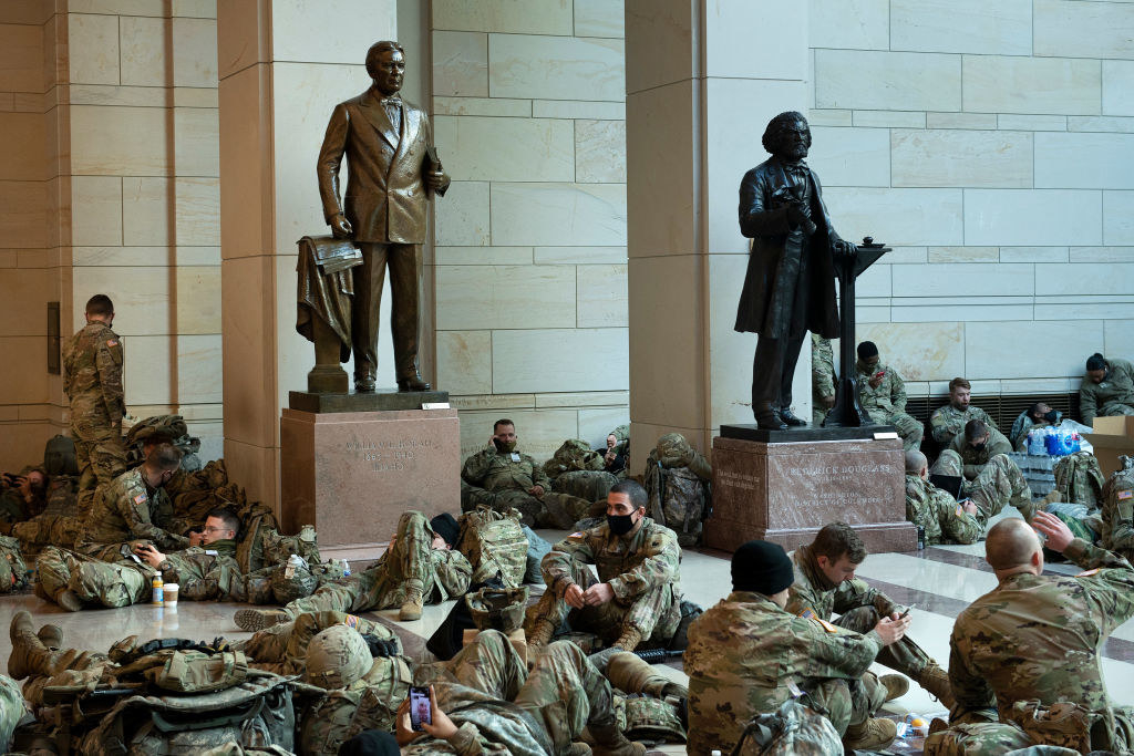 National Guard members sitting around two statues inside the Capitol